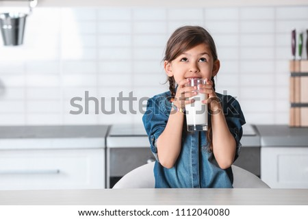 Cute little girl drinking milk at table in kitchen Royalty-Free Stock Photo #1112040080