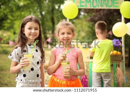 Little girls with natural lemonade in park #1112071955