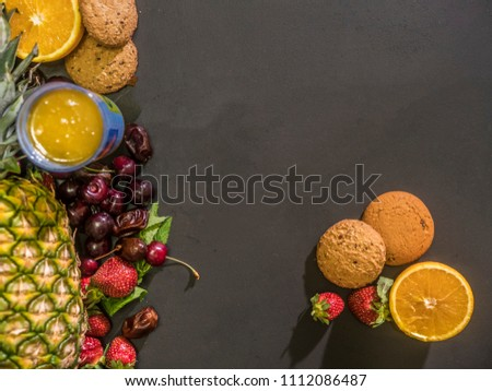fresh fruits berries cookies sweeties and juice on the black chalkboard overhead flat lay with copy space #1112086487