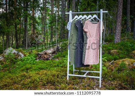 Clothes hanger with dresses in the woods. Concept for organic clothes, eco-friendly, ecological fashion. #1112095778
