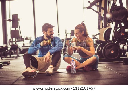Young couple at gym eating healthy food after exercise. #1112101457