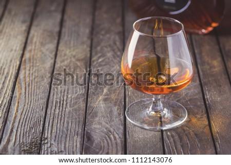 Glasse of brandy or cognac and bottle on dark background. #1112143076