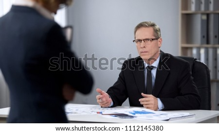 Angry male director looks at assistant, employment termination, poor performance Royalty-Free Stock Photo #1112145380