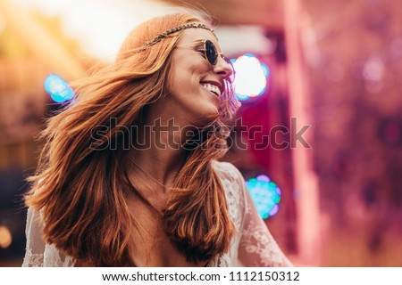 Beautiful young hippie woman enjoying at music festival outdoors. Woman in retro look dancing at music festival. #1112150312