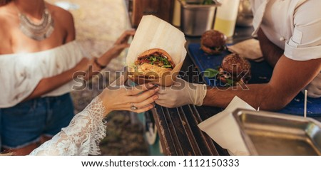 Woman hand reaching for a burger at food truck. Closeup of food truck salesman serving burger to female customer. #1112150333