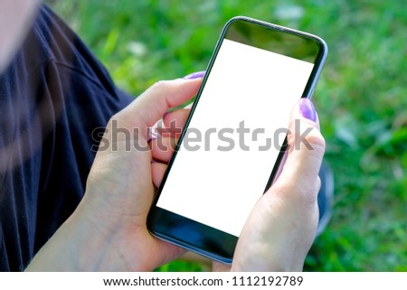The girl is sitting on the grass and looking into the smartphone holding it in her hands. Mockup image. #1112192789
