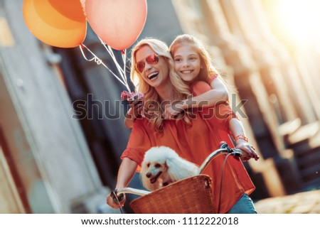 Mom and daughter are having fun in the city,riding a bike. #1112222018
