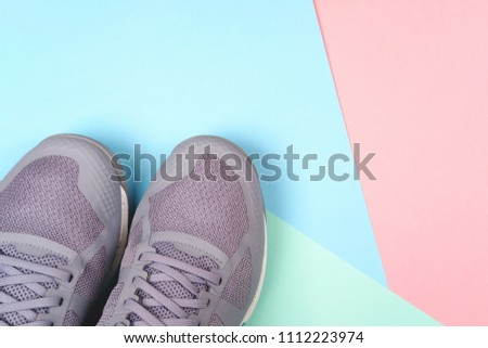Grey sneakers on multicolored pastel background. Concept of healthy life, everyday training and force of will. #1112223974