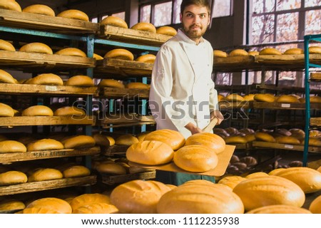 Baker. A young handsome bakery worker on the background of bread, takes bread from a stove with a wooden shovel. Industrial production of bakery products. a man in the baker's special clothing. Bakery #1112235938