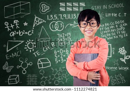 Picture of nerdy schoolgirl carrying a book while standing with scribbles on the chalkboard. Shot in the classroom