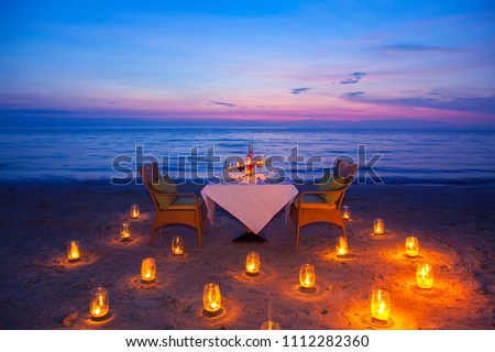 glass of wine And equipment on a wooden table with seascape and skyline in the evening with sunset tone style,Sunset is a romantic candlelight. #1112282360