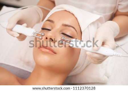 Young client of cosmetic salon having relaxing procedure on her face with special devices #1112370128