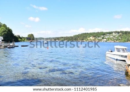 Seascape from the Tromøy island, Arendal city, Norway. The beautiful natural clear sea water and blue sky under the nice sunny day. View from the land.   #1112401985