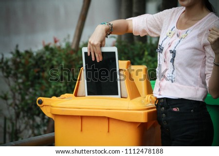 a woman dump tablet to yellow recycle bin in a park as future electronic garbage concept #1112478188