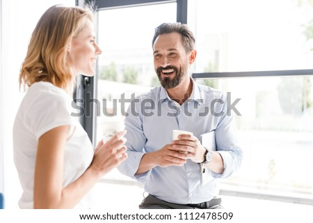 Couple of cheerful colleagues talking while standing at the office window with cups of coffee Royalty-Free Stock Photo #1112478509