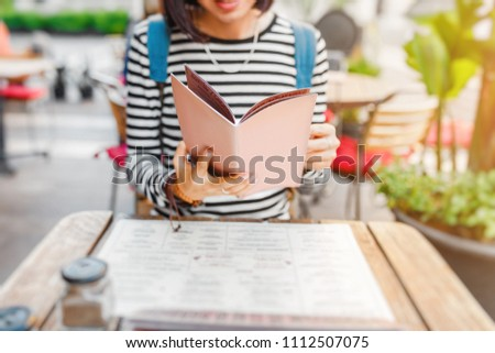 Young beautiful traveler woman in reading the menu and making an order at the terrace of cafe, local cuisine concept #1112507075