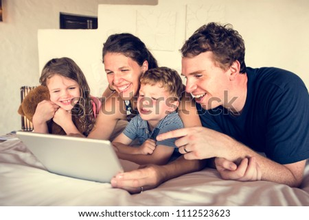 Family using a laptop in bed #1112523623