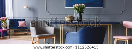 Chairs standing by the blue and gold dining table with pink roses in vase in dark grey open space living room interior #1112526413