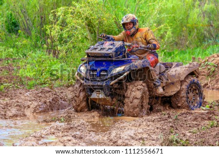 Russia, Samara, June 2017: the quad bike is moving along the mud. Catching on quad bikes on impassability, a favorite occupation of extreme men in Russia. #1112556671