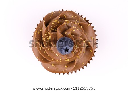 Cupcake with whipped chocolate cream, decorated fresh blueberry, gold confectionery sprinkling on white background. Picture for a menu or a confectionery catalog. Top view.