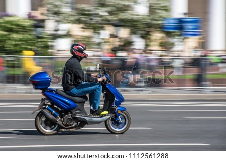 Russia, Moscow - May 13, 2018: Man on scooter speeding through the central street of the city #1112561288