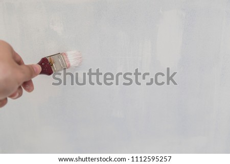 Painting of walls in a white color. Repair in a house. #1112595257