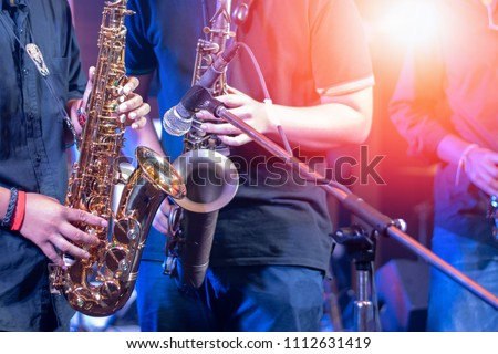 Saxophone with microphone, music instrument played by saxophonist player musician in pub fest.The Fête de la Musique,  Make Music Day and World Jazz Day concept.  #1112631419