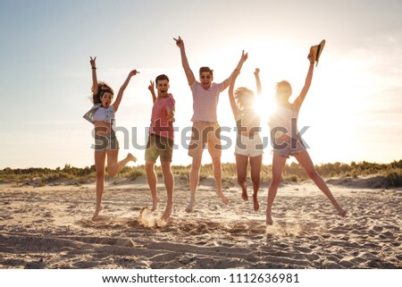 Group of cheerful young friends dressed in summer clothes jumping together with hands raised at he beach #1112636981