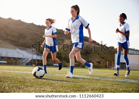Group Of Female High School Students Playing In Soccer Team #1112660423