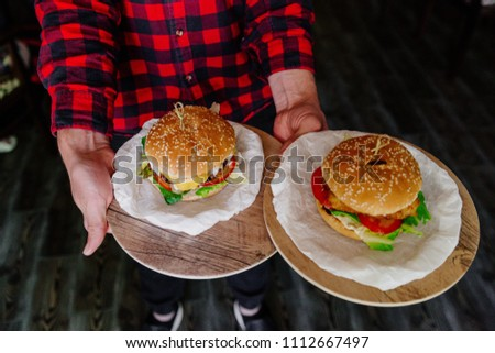 burgers in the hands of the waiter #1112667497