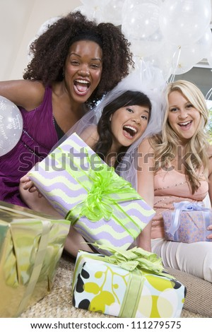 Portrait of multiethnic friends with gifts screaming at party #111279575