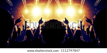 Concert venue crowded with fans, raised hands are visible #1112797847