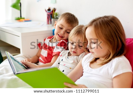 childhood, leisure and family concept - little kids reading book in bed at home #1112799011