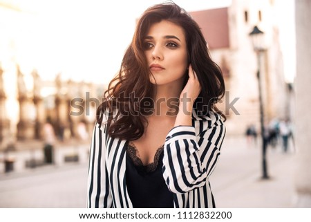 Photo of beautiful stylish brunette woman in the city ,wearing sunglasses, black and white stripes shirt. Fashion summer photo #1112832200