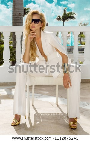Beautiful, elegant woman in a white suit posing on the background of the caribbean palms #1112875241
