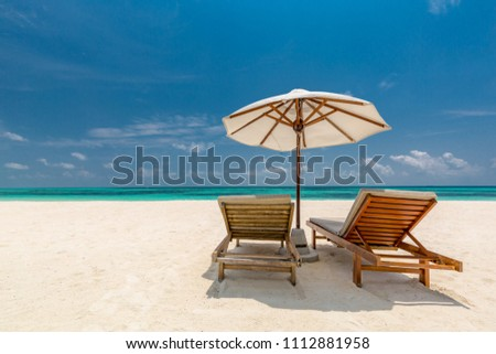 Perfect beach scene. Sun lounger and umbrella on tranquil beach landscape, white sand and blue sky. Romantic summer vacation background concept #1112881958
