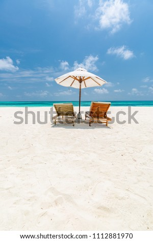 Idyllic beach background. Romantic beach scene with sun chairs and umbrella, tranquil tropical landscape in vertical crop and soft colors process #1112881970