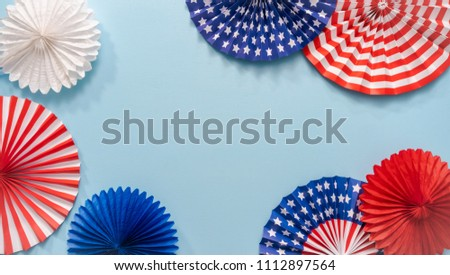 July 4th theme paper fans on blue background. #1112897564