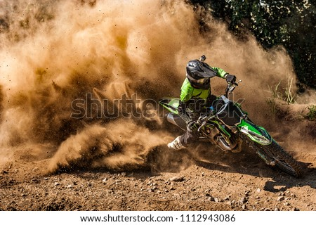 Motocross rider creates a huge cloud of dust and debris #1112943086