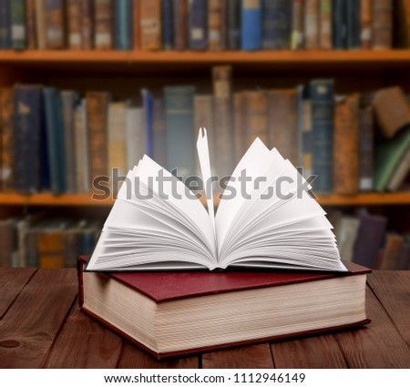 Open old book on a bookshelf background #1112946149