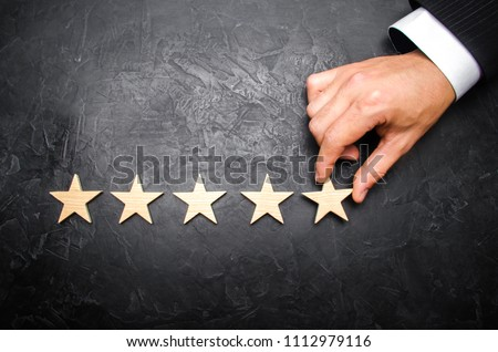 The businessman's hand in the suit holds the fifth star. Get the fifth star. The concept of the rating of hotels and restaurants, the evaluation of critics and visitors. Quality level, good service. #1112979116