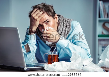 Bad feeling. Sick worker has high temperature. Photo of young man in office suffering virus of flu. Medical concept. Royalty-Free Stock Photo #1112983769