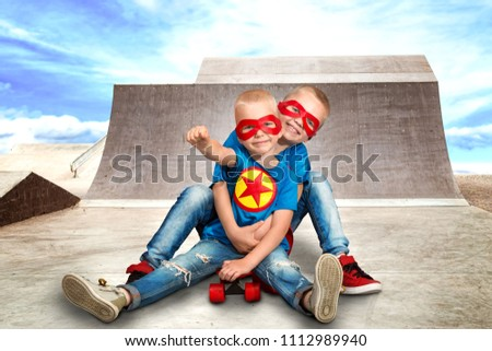 Children  in superhero costumes riding on steep hills to skateboard at the skate Park.Extreme sports.	 #1112989940