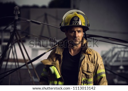 Firefighter with uniform and helmet stand in front of electric wire on a roof top #1113013142