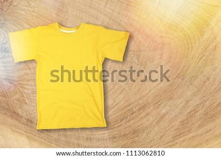 Mockup of blank colorful tshirt on desk #1113062810