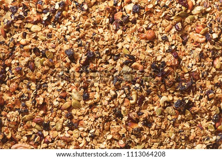 Organic homemade roasted granola with nuts and raisins on baking sheet. Food for breakfast. Meal background, granola texture. #1113064208