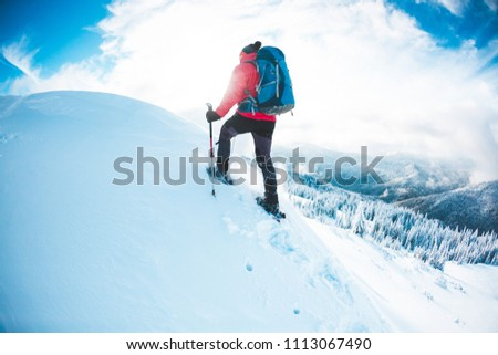 A man in snowshoes in the mountains in the winter. A climber with trekking sticks walks through the snow. Winter ascent. Beautiful sky with clouds. #1113067490