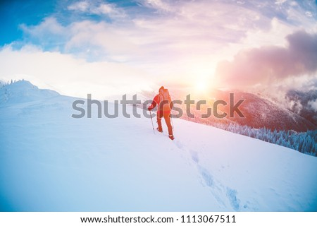 A man in snowshoes and trekking sticks in the mountains. Winter trip. Climbing of a climber against a beautiful sky with clouds. Active lifestyle. Climbing the mountain through the snow. #1113067511