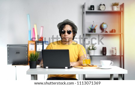 Working From Home. Young Man Working With Laptop Wearing Fedora Hat on Summer Vacation Season at Office #1113071369