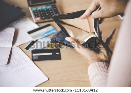 poor Asian woman hand open empty purse looking for money having problem  bankrupt broke after credit card payday Royalty-Free Stock Photo #1113160412
